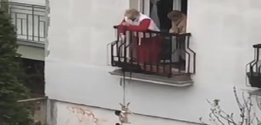 في زمن كورونا .. مسنة تنزل كلبها من شرفة منزلها لأخذ نزهة فى الهواء