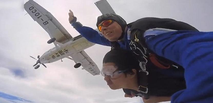 شاب صينى يتحدى إصابته بضمور العضلات بتجربة القفز بالمظلة والغوص